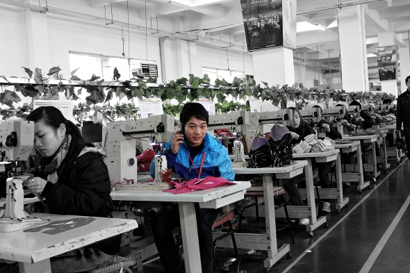 Factory boy on phone in Anta Shoe Factory China