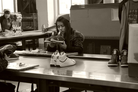 A girl sizes up the shoes to make sure they are correctly paired.